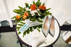 Wedding shoes, garter, white pillow with wedding rings, bouquet on a table.  Stock Photography