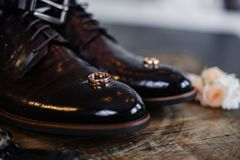 Wedding shoes of the groom on a dark background. Stand with a boutonniere royalty free stock photos