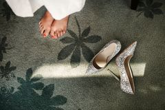 Wedding shoes and legs of the bride stock image