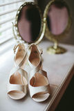 Wedding Shoes with Mirror. Ivory satin wedding heels for the bride placed in front of an elegant golden mirror before the wedding ceremony Stock Images