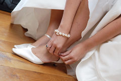 Wedding shoes preparation. Wedding preparation detail with bride tying up her white shoes Stock Image