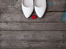 Wedding shoes and red heart on wood background Royalty Free Stock Photos