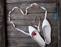Wedding shoes and ribbon in the form of heart on wood background Royalty Free Stock Image