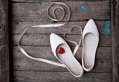 Wedding shoes and ribbon in the form of heart on wood background Royalty Free Stock Photos
