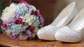 Wedding shoes rings bouquet of flowers. Close up of wedding decoration made of beautiful white shoes, wooden stand for wedding rings and bouquet of flowers stock video