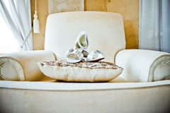 Wedding Shoes on Sofa. White wedding shoes on a cream color sofa and cushion stock photos