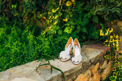 Wedding shoes on a stone border against a background of green leaves Royalty Free Stock Photo