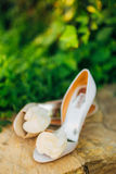 Wedding shoes on a stone border against a background of green leaves Stock Image