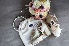 Wedding shoes, tiara and bouquet on a gray background.  Stock Image