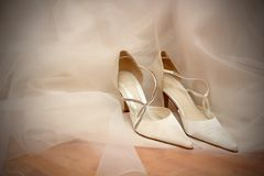 Wedding shoes on White bridal dress. Royalty Free Stock Photo