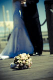 Wedding shot. Focused bouquet on the ground while wedding couple on the background Royalty Free Stock Photos