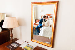Wedding shot of beautiful bride and groom kissing next to mirror in the hotel room Stock Photos