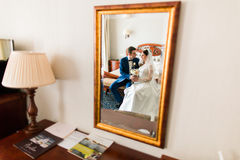 Wedding shot of beautiful bride and groom  sitting next to mirror in the hotel room Royalty Free Stock Photography