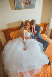 Wedding shot of bride and groom lying in a stylish bed Stock Images