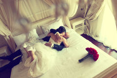 Wedding shot of bride and groom lying in a stylish white bed red flower bouquet Stock Photos