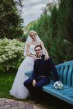 Wedding shot of bride and groom sit on bench in park Stock Image