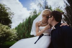 Wedding shot of bride and groom sit on bench in park Stock Photo