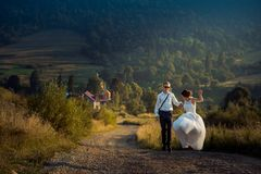 Wedding shot of the joyful attractive just married in sunglasses dancing o nthe road at the background of the mountains. During the sunset Royalty Free Stock Photography