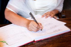Wedding signature. Bride write on registration of marriage Royalty Free Stock Photography
