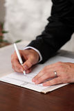 Wedding signature. Groom signs the marriage document Royalty Free Stock Photos