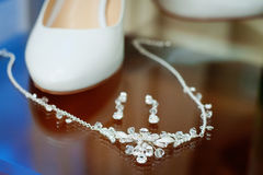 Wedding silver jewelry and bride shoes stock images