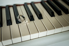 Wedding silver rings lying on the piano keys Royalty Free Stock Photography