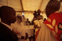 A wedding in South Africa. The bride and groom stood next to the Priest with guests looking on Stock Image