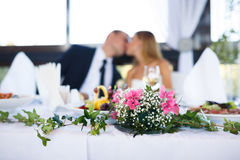 Wedding special moment (focus on flowers). Wedding Kiss at the banquet (focus on flowers stock photography
