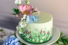Wedding spring cake decorated with colorful flowers and hydrangeas. Desserts for a festive summer mood. Wedding spring cake decorated with beautiful flowers and Stock Images