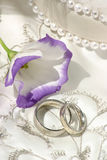 Wedding still life. Wedding bands sitting on top of richly embroidered wedding dress with white and purple flower stock images