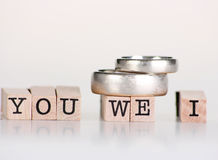 """Wedding still life. Wedding rings sitting on top of wooden stamps saying """"You We I stock image"""