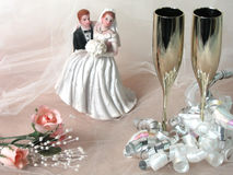 Wedding Still Life. Bride and groom figurine, champagne flutes, curly silver and white ribbon, peach roses on white netting stock image