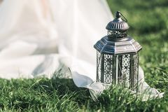 Wedding still life black lantern on grass and white tule in rustic style. Stock Photo