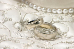 Wedding still life with dress. Wedding bands sitting on top of richly embroidered wedding dress royalty free stock photos