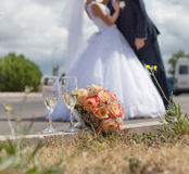 Wedding still life. Nosegay and wine glass on background of unrecognizable kissing groom and bride Stock Photography
