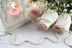 Wedding still life. Romantic wedding still life with roses, pearl necklace and candle in latern Royalty Free Stock Images