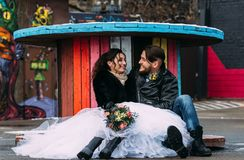 Wedding in the style of rock. Rocker or Biker wedding. Guys with stylish leather jackets. It`s a rock`n`roll baby! A sweet couple is photographed against the stock image