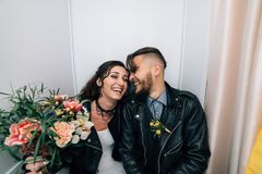 Wedding in the style of rock. Rocker or Biker wedding. Guys with stylish leather jackets. It`s a rock`n`roll baby The sweet couple are photographed in a stock images