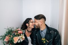 Wedding in the style of rock. Rocker or Biker wedding. Guys with stylish leather jackets. It`s a rock`n`roll baby! The sweet couple are photographed in a royalty free stock image