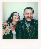 Wedding in the style of rock. Rocker or Biker wedding. Guys with stylish leather jackets. It`s a rock`n`roll baby! The sweet couple are photographed in a stock image