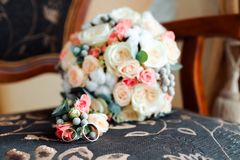 Wedding stylish bouquet with purple roses and rings. Wedding stylish bouquet with purple roses, pink roses and white flowers royalty free stock images