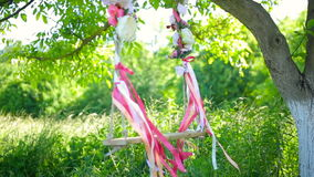 Wedding swing decorated with flowers hanging on the branches. Of the old willow stock video footage
