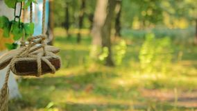 Wedding swing decorated with rope hanging on the branches of the old willow. HD stock footage