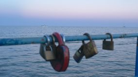 Love locks hanging on bridge in background of sea and ships stock video