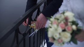 Wedding symbol, lock in hands of bride and groom. Newlyweds fix the lock on the bridge as a symbol of love. Padlock in Royalty Free Stock Photos