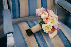 Wedding symbol. Wonderful wedding bouquet lies on vintage armchair, prepared for special occasion. Flowers stock photos