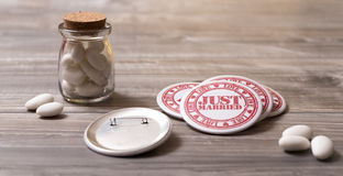 Wedding symbols: sugar almonds and just married pins. Table with sugar almonds and just married pins Royalty Free Stock Photos