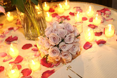 Wedding Table. Flower petals, bouquet, candles and guest book adorn wedding table at reception entrance Stock Photos
