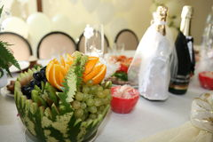 Wedding table. There is a meal on a wedding table: two bottles of champagne, fruit basket, water-melon,grapes, oranges Royalty Free Stock Photo