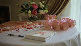 Wedding table appointments. Table with wedding decor, wish book, rose petals, pen. Wedding album, book wishes to the newlyweds stock footage